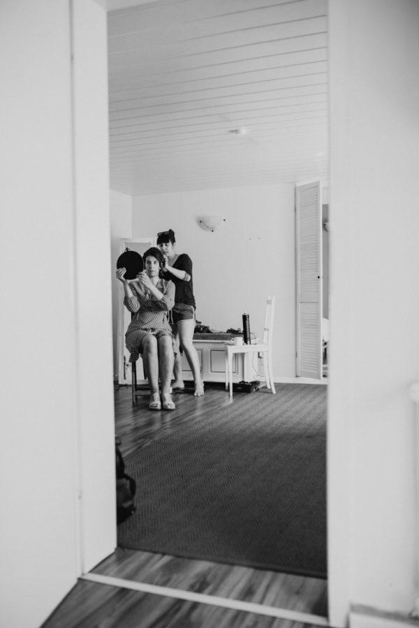 Braut wird gestylt und schaut in den Spiegel