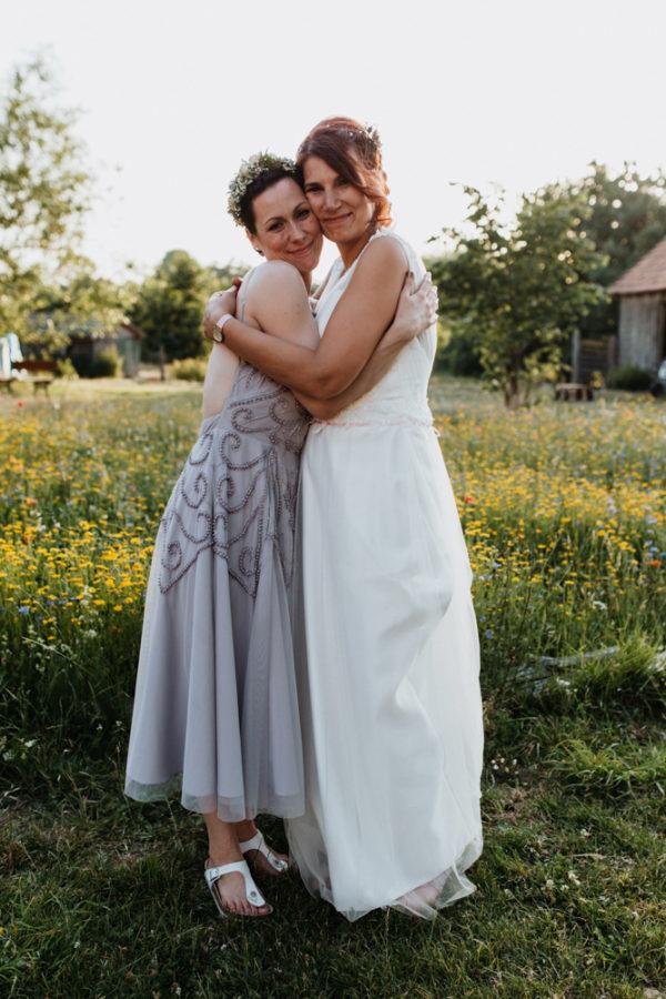 Braut mit Trauzeugin, sie umarmen sich