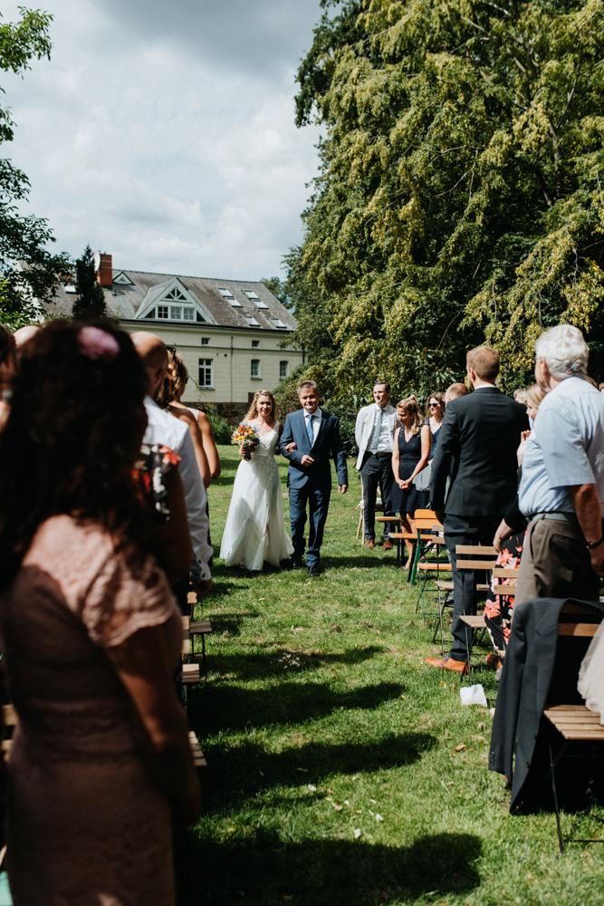 Boho Hochzeit in Bekemühle in Brandenburg. Braut und Vater laufen ein