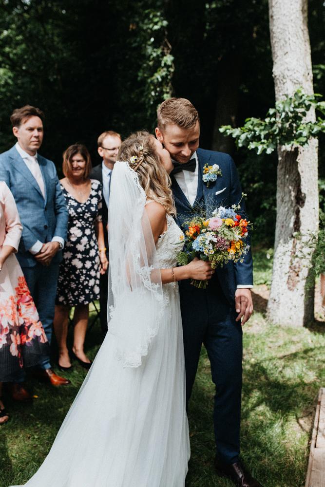 Boho Hochzeit in Bekemühle in Brandenburg. Braut küsst Bräutigam auf die Wange.