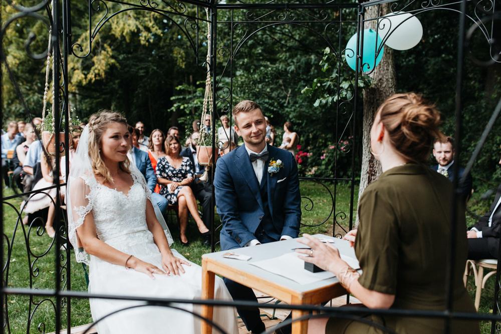 Boho Hochzeit in Bekemühle in Brandenburg. Brautpaar sitzt gegenüber der Traurednerin.