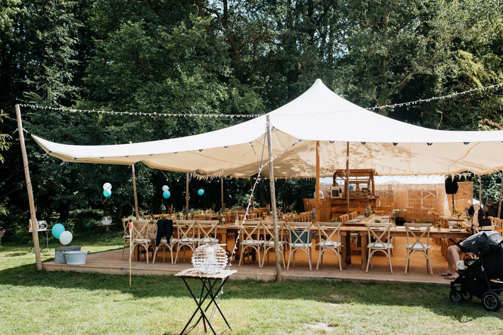 Hochzeit Boho in Bekemühle in Brandenburg. Ein Zelt mit Stühlen und Tischen darunter, hübsch dekoriert.