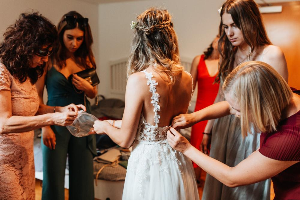 Hochzeit Boho in Bekemühle in Brandenburg. Freundinnen helfen die Braut anzuziehen.