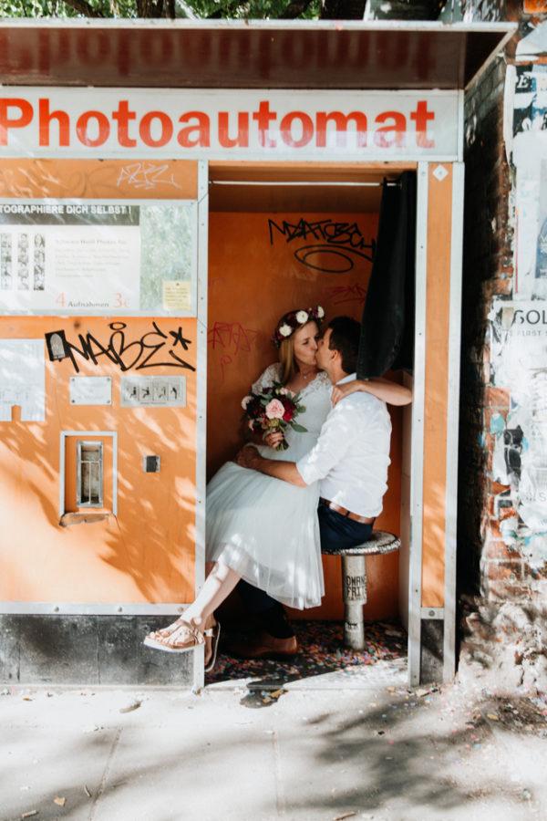 Boho Hochzeit Shooting in Berlin. Brautpaar sitzt zusammen im Fotoautomat.