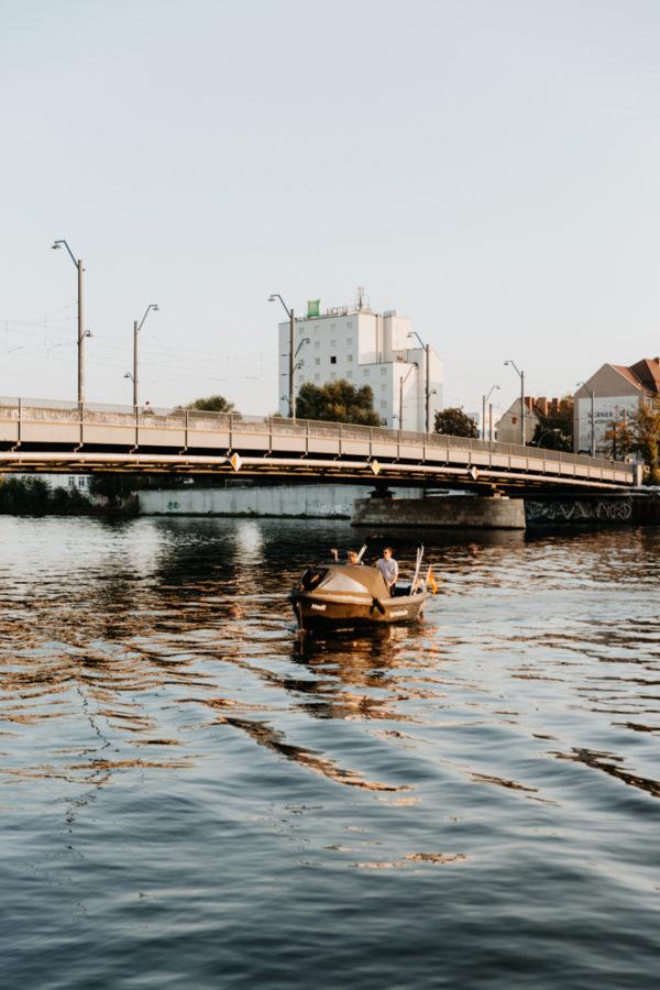 Boho Hochzeit in Berlin. Das Brautpaar kommt auf einem Boot angefahren.