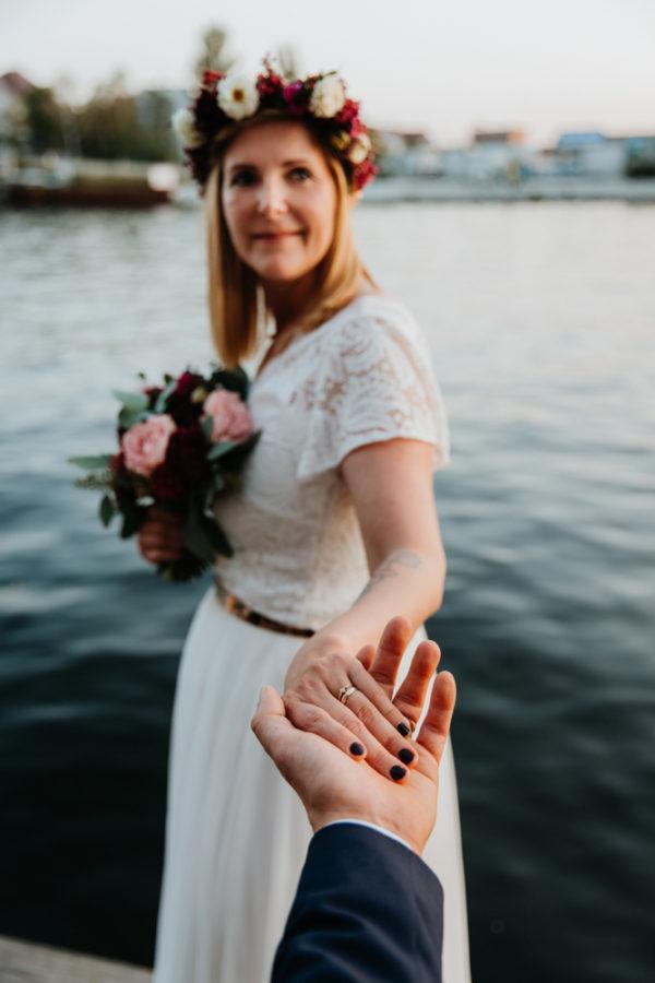 Boho Hochzeit in Berlin. Bräutigam hält die Hand der Braut.