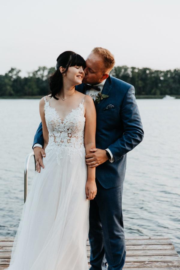Hochzeit Shooting in Gnewikow bei Neuruppin. Bräutigam küsst seine Braut auf die Wange.