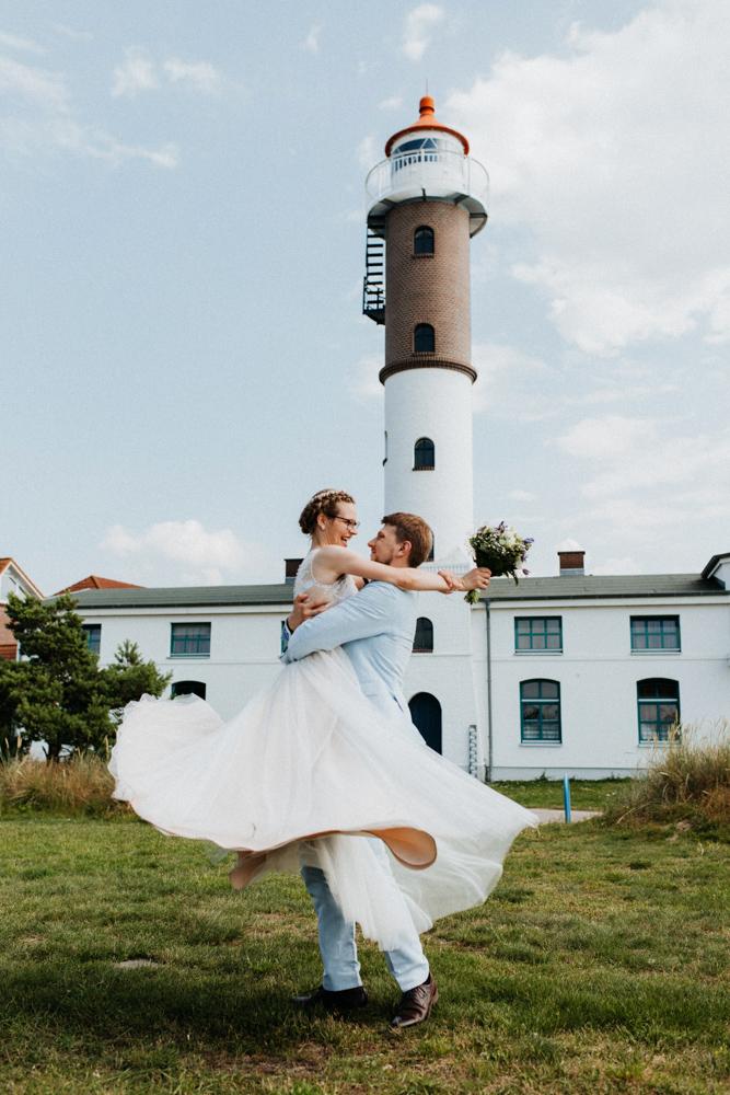 Hochzeit Shooting am Timmendorfer Strand an der Ostsee. Bräutigam hebt Braut hoch und dreht sich.